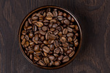 bowl of coffee beans on a dark background, top view