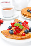 Breakfast with pancakes, fresh berries and black tea on white