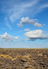 Agriculture, plowed land after wheat harvest with beautiful sky