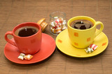 Yellow and orange cup of coffee with colorful candies