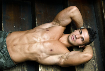Attractive muscular young man laying on steps of wooden stair
