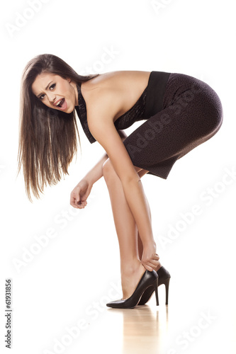 nervous young woman puts on her high heels