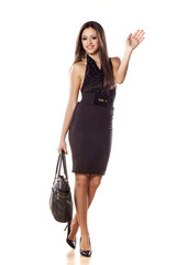 business woman posing with handbag and wave her hand