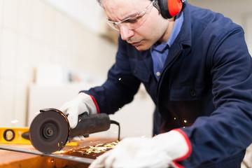 Worker grinding a metal plate