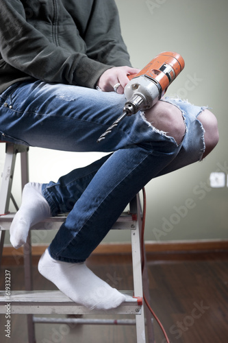 Young female holding a drill while sitting on ladder