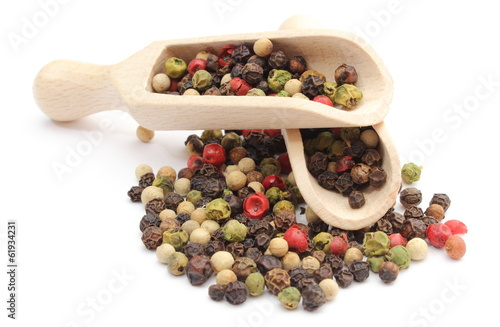 Colored pepper on a wooden spoons isolated on white background