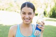 Happy sporty woman holding water bottle