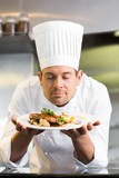 Male chef with eyes closed smelling food in kitchen