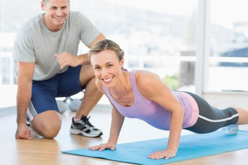 Woman doing push ups with trainer