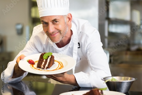 Smiling male pastry chef with dessert in kitchen