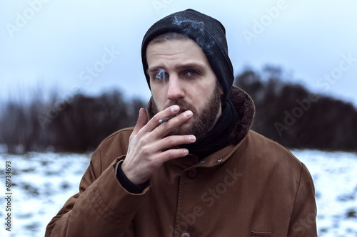 Beautiful brutal bearded man with a cigarette on the street