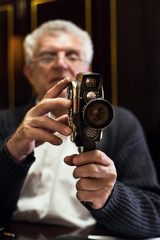 Senior man holding old fashioned Movie Camera.