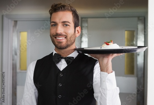 Smiling waiter holding tray with plate of dessert