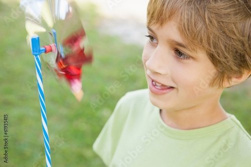 Boy looking at pinwheel in park