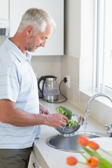 Casual man rinsing broccoli in colander