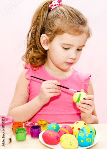 Cute little girl painting easter eggs