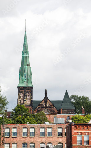 Green Steeple Beyond Old Brick Buildings