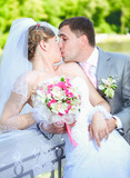 portrait of newly married couple kissing at park at sunny day