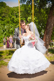 Handsome groom swinging bride on playground and hugging her