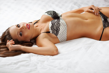 woman wearing lingerie lying on bed
