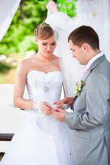 Handsome groom putting wedding ring on brides hand at alcove