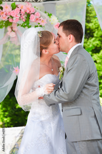 Newly married couple standing in alcove and kissing