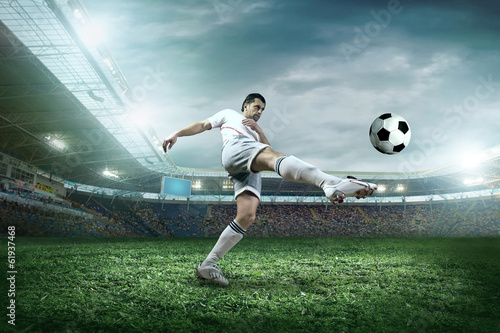 canvas print picture Soccer player with ball in action outdoors.