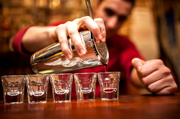 barman hand with shake mixer pouring beverage into glasses