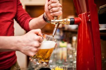 Barman brewing a draft, unfiltered beer at pub or bar