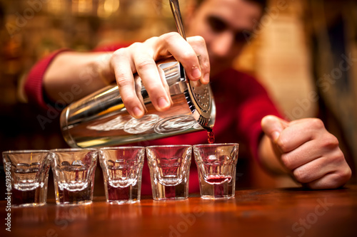 Fotobehang Bar barman hand with shake mixer pouring beverage into glasses