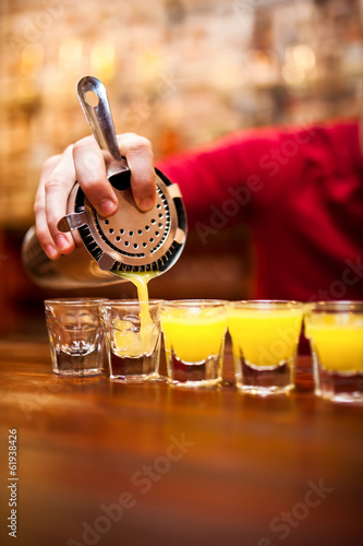 Bartender pouring strong alcoholic drink into small glasses