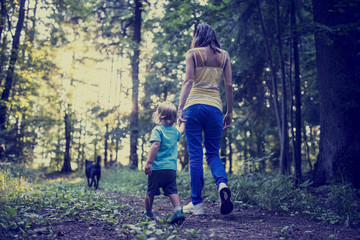 Woman and child walking a dog in the forest