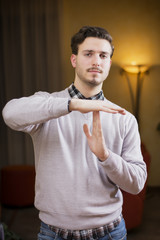 Attractive young man doing time-out sign