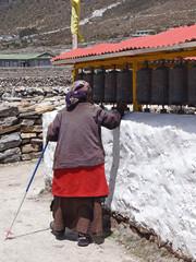 Femme âgée tournant les moulins à prière à Khumjung - Népal