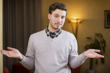 Confused or doubtful young man shrugging with palms open