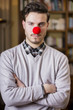 Serious young man with red clown nose