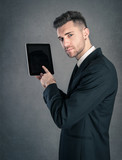 Young businessman showing tablet against dark grunge background.