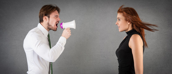 Man shouting to woman with megaphone against grunge background.