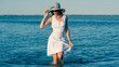 Young woman wearing white dress and hat walking at the beach.