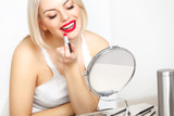 Red lips. Beautiful Woman Doing Daily Makeup. Lipstick applying