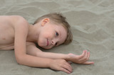 little boy lying on the sand