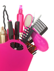 Various hairstyling equipment in shopping bag isolated on white