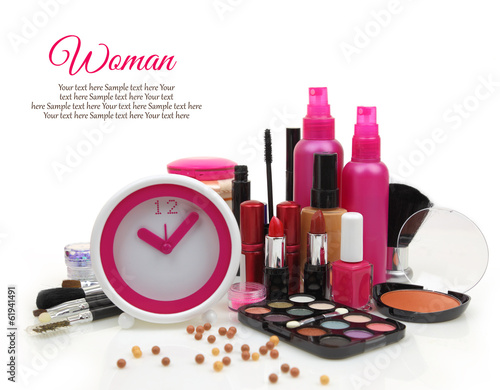 Pink clock with various cosmetics isolated on white background