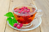 Tea with raspberry and leaf in a cup on board