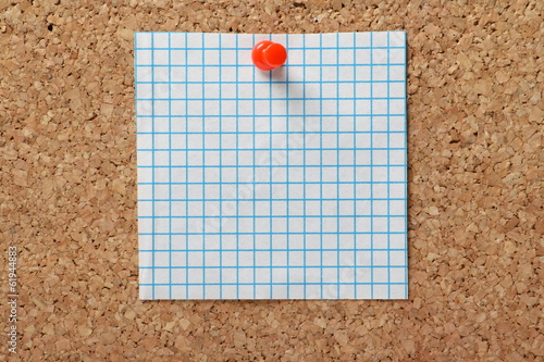 A square of blue graph paper pinned to a cork notice board
