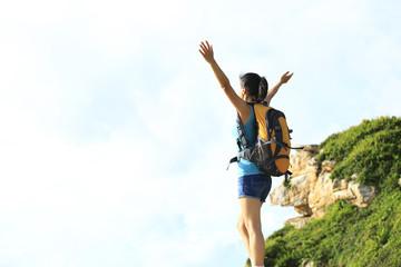 cheering young woman hiker mountain peak