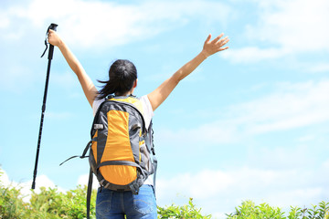 cheering woman hiker open arms at seaside mountain peak