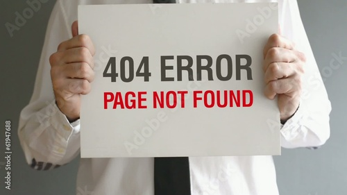 Businessman holding paper with 404 Error - Page not found title.