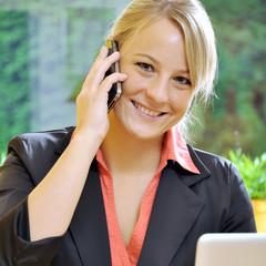 Geschäftsfrau im Büro telefoniert mit Smartphone