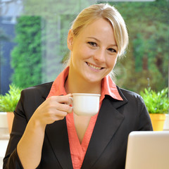 Geschäftsfrau im Büro trinkt Kaffee